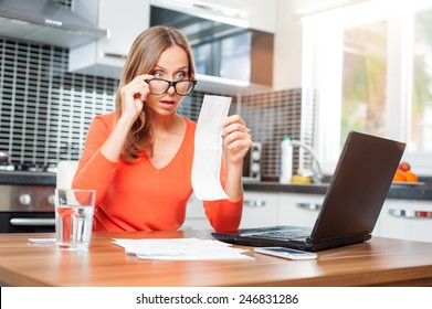stressed over bills. Surprised young woman looking at her financial debts in the kitchen at home wearing orange pullover sitting at dining table.