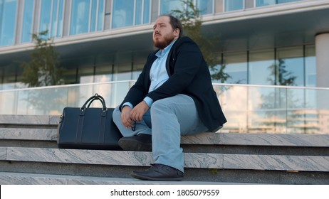 Stressed overweight businessman in formal wear sitting on street stairs worried about problem at work. Depressed fired office worker sitting on staircase outside modern business center