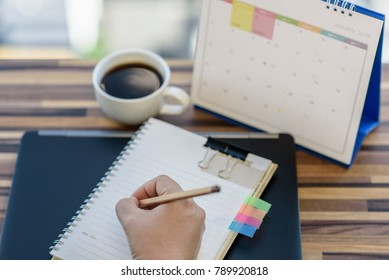Stressed planner writing on diary with blur calendar January 2018, Laptop, coffee on table. Event organizer writing details of plan, timetable, timeline, schedule, Calendar 2018 Concept.
