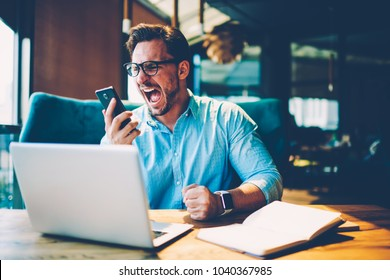 Stressed proud ceo scream with aggression in mobile phone on employe due to failed project working remotely at laptop computer in cafe. Dissatisfied businessman is angry during hate cellular calling