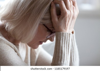 Stressed sad tired middle aged senior woman holding head in hands feeling headache migraine concept, upset old elderly mature lady in panic suffering from pain, alzheimer disease, anxiety depression