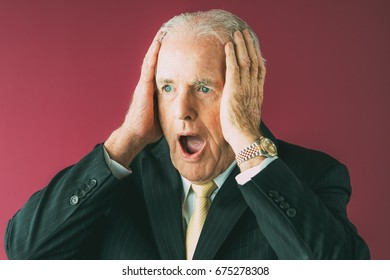 Stressed Senior Business Man Clutching Head