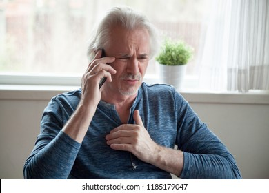 Stressed senior mature man feeling pain having heart attack talking on phone hearing bad news, old middle aged male calling emergency touching chest suffer from heartache disease at home, infarction