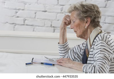 Stressed Senior woman checking finance with calculator at home