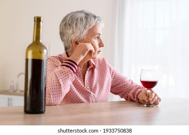 Stressed senior woman drinking wine at home