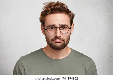 Stressed sorrorful bearded man curves lower lip as sustains defeat. Disappointed unshaven male feels upset, spends time home alone, being lonliness, has regretful expression stands over studio wall