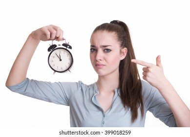 Stressed student with clock in her hand pointing at 11:55