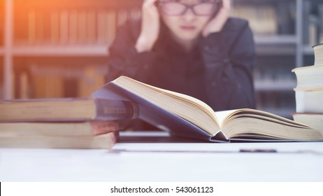 Stressed student in front of books. Student getting confused before exams. Preparing for final exam.