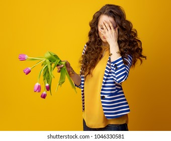 stressed stylish woman in striped jacket against yellow background with wilted flowers