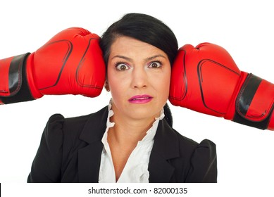 Stressed surprised executive woman with her head under boxing gloves pressure against white background