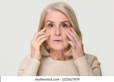 Stressed surprised old mature woman looking at camera worried about facial wrinkles, middle aged senior lady touching aging face skin isolated on white grey studio background, skincare, portrait