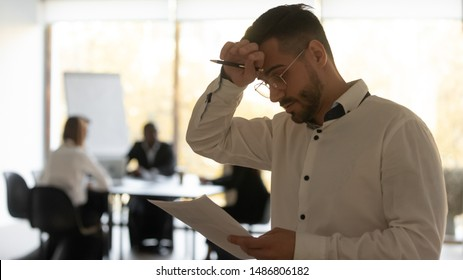 Stressed sweaty inexperienced businessman male speaker sweating wiping sweat holding paper reading preparing for speech feeling nervous worried tedious waiting afraid of public speaking fear concept