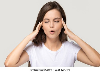 Stressed teen girl calming down relieving headache emotional stress relief, nervous young woman meditating massaging temples doing breathing exercises isolated on white grey studio blank background