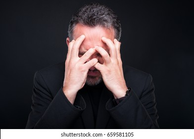 Stressed or tensed classy man looking very angry because of a problem isolated on black background