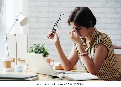 Stressed or tired business lady rubbing her eyes