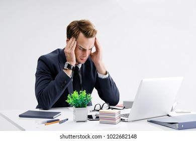 Stressed, tired businessman or heaving headache, holding his head, in black suit, working with laptop computer at office. Business fall, job and education concept.
