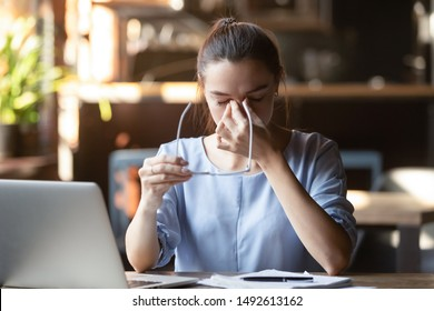 Stressed tired female student holding glasses feeling eye strain headache after computer work sit at table overworked suffer from pain in dry irritated eyes bad blurry weak vision problem concept
