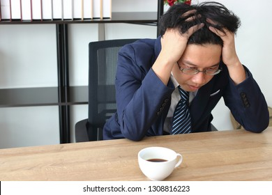 Stressed tired young Asian business man with hands on face feeling depression in workplace of office.