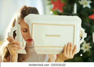 stressed trendy woman with a broken dish near Christmas tree