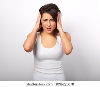 Stressed unhappy crying casual woman with head pain closed ears the hands because not want the hear any sounds and noise.