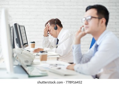 Stressed unhappy mature stock broker at his workplace