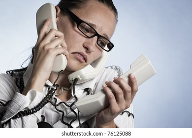 Stressed unhappy telephonist in call center wrapped with phone cables being over-strained with work, isolated on blue background.