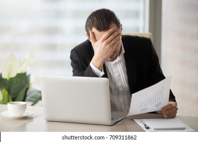 Stressed unhappy young businessman in office in front of laptop, holding financial document and facepalming in disbelief because of failing report statistics. Fall in liquidity of stocks, finance loss