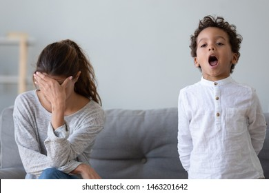 Stressed upset mother tired about stubborn african kid tantrum feeling desperate having headache from screaming mixed race child annoyed with naughty difficult little son demanding attention at home