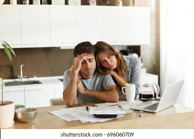 Stressed wife and husband with many debts doing paperwork together, reviewing their expenses, planning domestic budget and calculating bills in kitchen, surrounded with papers, calculator and laptop