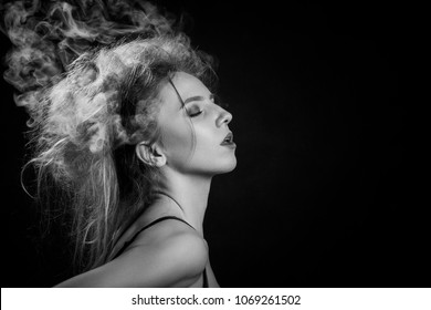 stressed woman with cloud of smoke on her head on black background, monochrome