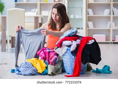 Stressed woman doing laundry at home