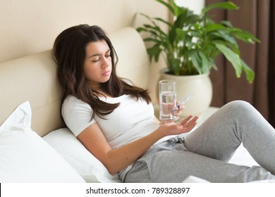 Stressed woman drinking pill or medicine with glass of water on bed at home after wake up in the morning