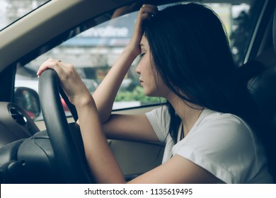 Stressed woman driver sitting in car having headache stop after driving car in traffic jam on rush hour.  Exhausted, overworked driver automobile transportation concept.