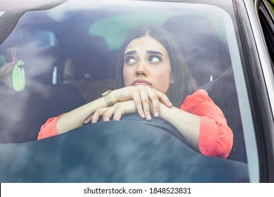 Stressed woman driver sitting inside her car. Angry female driver driving a car. Angry young woman stuck in a traffic jam. Woman annoyed in car. Girl stuck in traffic.