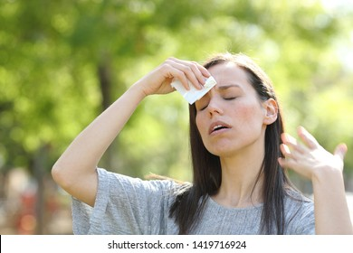Stressed woman drying sweat using a wipe in a warm summer day in a park