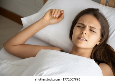 stressed woman with grinding teeth, bruxism symptoms; portrait of stressful, exhausted, tired sleeping woman grinding teeth with stress; oral, dental care medical concept; caucasian adult woman model