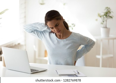 Stressed woman having health problem, feeling back pain, sitting at workplace, massaging, touching back, female student suffering from backache after long sedentary work with computer