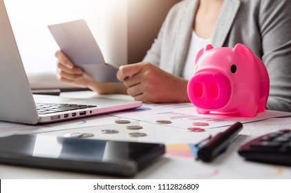 Stressed Woman holding account passbook. Calculator, Pink Piggy Bank, Laptop, business chart and graph document on desk. Debt.