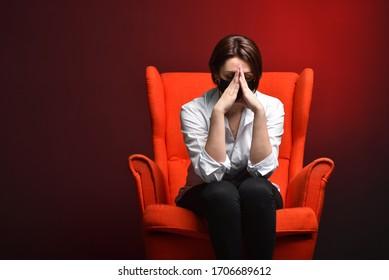 Eine gestresste Frau hält den Kopf, während sie in einem roten Stuhl sitzt, während ein Test und eine Koronavirus-Pandemie durchgeführt werden. Das Konzept der viralen Gefahr und Angst