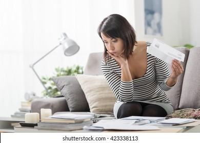 Stressed woman at home checking expensive electricity and household bills, home finance concept