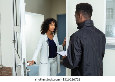 Stressed Woman Opening Door To Bailiff At Home