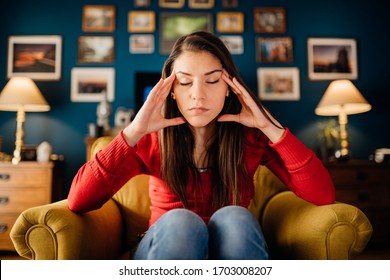 Stressed woman overthinking events alone at home.Thinking of problems.Concentration problems.Brain/cognitive/neurological activity stimulation.Memory loss.Headache,migraine,high blood pressure,anxiety