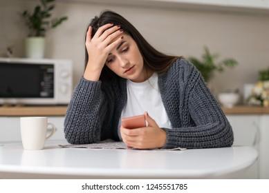 Stressed woman reading something on her cell phone at home