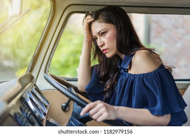 stressed woman sitting inside a vintage car