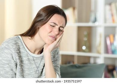 Stressende Frau, die Zahnschmerzen leidet, klagt über die berührende Wange auf einem Sofa zu Hause