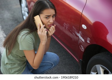 Stressed woman talking on phone near car with scratch outdoors