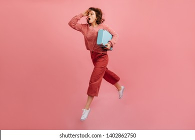 Stressed woman with valise hurrying on pink background. Studio shot of running lady with suitcase.
