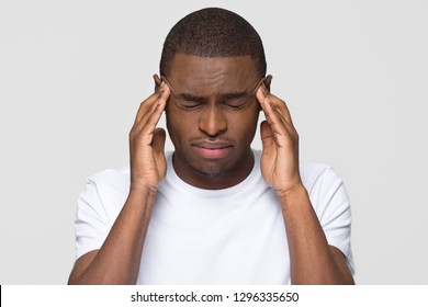 Stressed young african american man feel pain having terrible strong headache concept, tired upset black guy massaging temples suffering from migraine isolated on white grey studio blank background
