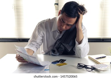 Stressed young Asian man with business office wear holding bills and another hand on head, thinking about  finding money to pay credit card debt and all bills. Financial problem concept.