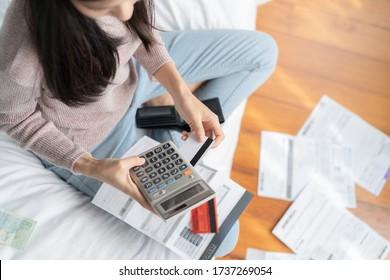 gestresste junge Asiatin berechnet monatliche Kosten und überprüft Kreditkartenrechnungen.